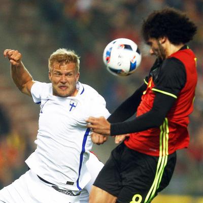 Paulus Arajuuri i närkamp med Marouane Fellaini.