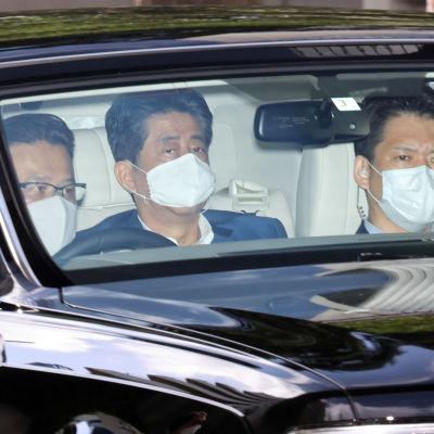 Tre japanska män sitter i en bil och de har munskydd på sig. En av männen är Japans premiärminister Shinzo Abe.
