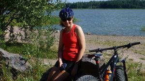 Maarit Tuomisto vid en strand med cykelhjälm på huvudet och en cykel bredvid sig.