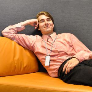 nuori hymyilevä mies makaa rennosti sohvalla