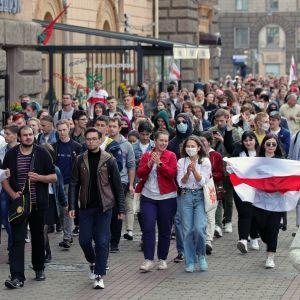 Joukko opiskelijoita marssii kadulla. Monet kantavat punavalkoisia lippuja.
