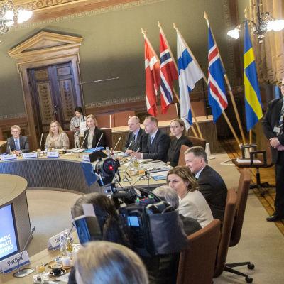 Nordiska ministrar samlade kring mötesbord medan fotografer fotograferar dem.