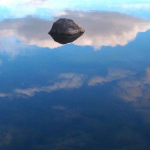 Kivi  nousee tyynestä merestä, johon kirkas taivas poutapilvineen heijastuu.