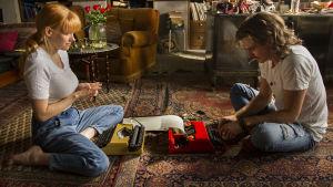 Inka och Juhana sitter på en orientalisk matta på golvet och skriver på varsin skrivmaskin.