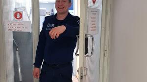 Poliisi seisoo tilannekeskuksen ovella.