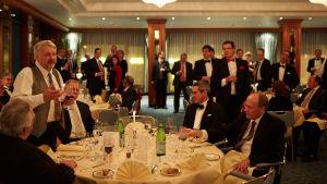 Festfolk runt ett bord, en man håller ett tal
