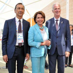 Sala, Pelosi ja Hickey poseeraavat näyttelyhallissa. Pelosilla on turkoosi asu ja miehillä tummansiniseet puvut.