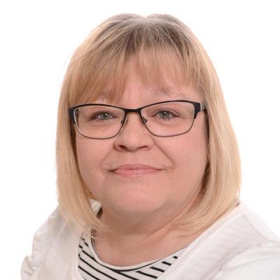 Kvinna med glasögon och blont hår som tittar rakt in i kameran.