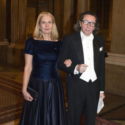 Katarina Frostenson i långklänning och Jean-Claude Arnault i frack, håller varandra i armkrok.