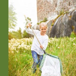 Bild på Raseborgs logo med borg och vitsippa, vit på grönt botten, och en flicka med blont hår och vit skjorta som springer över ett fält med en fjärilshåv. Raseborgs slott i bakgrunden.