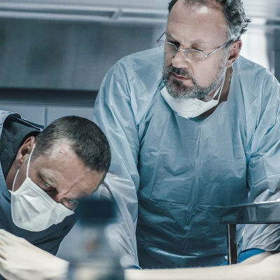 Sorjonen ja muut tutkijat tuijottavat ruumiinavauspöydällä naisen jalkaa. Heillä on päällään siniset suoja-asut.