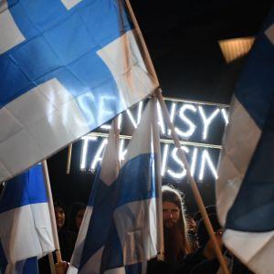 En man står bakom blåvita flaggor med ett plakat.
