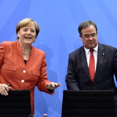 Angela Merkel och Armin Laschet på en presskonfes. Merkel ler medan Armin Laschet tittar ner i podiet.