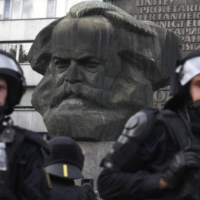 Chemnitzissä poliiseja Karl Marxin patsaalla, jonka vieressä mielenosoittajat kokoontuivat.
