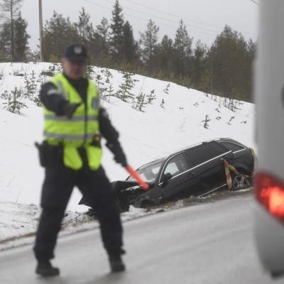 Polisen dirigerar trafiken vid olycksplats, olycksbil i diket bakom polisen.