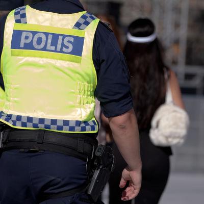 Kaksi poliisia huomioliivit päällään. Kuvassa mukana myös jalankulkijoita.