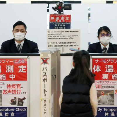 """En kontrollstation på en flygplats. På stationen står det """"kontroll av kroppstemperatur"""". Personalen har kostym och andningsskydd."""