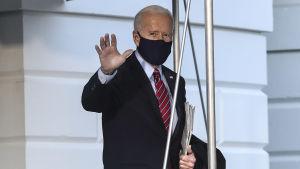Gråhårig man i kostym och munskydd vinkar åt kameran. President Joe Biden utanför Vita huset den 5 februari 2021, på väg till Wilmington i Delaware.