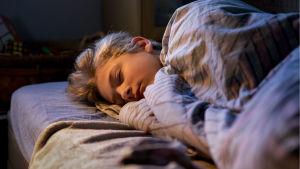 En tonårspojke sover i sin säng.