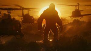 Kong står i solnedgången och ser hur en mängd stridshelikoptrar kommer flygande mot honom.