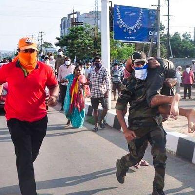 Människor springer på en gata, en person bär en annan på sin axel.