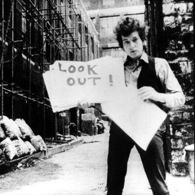 """Bob Dylan esittelee sanakylttejä """"musiikkivideossa"""" Subterranean Homesick Blues, taustalla Allen Ginsberg. Kuva D.A. Pennebakerin ohjaamasta dokumenttielokuvasta Don't Look Back (1967)."""