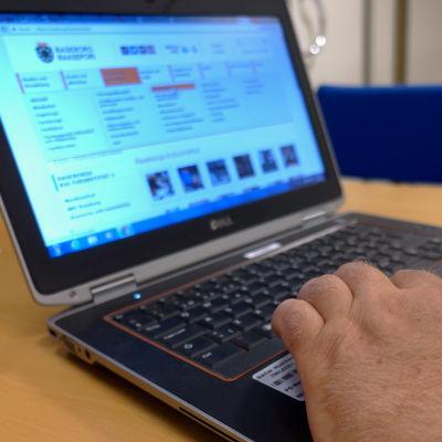 En bärbar dator med en hand på tangentbordet. På datorns skärm är Raseborgs stads hemsida öppen.