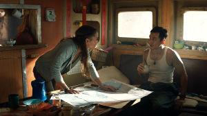Lara och Lu diskuterarf framtiden lutade över ett sjökort ombord på en båt.