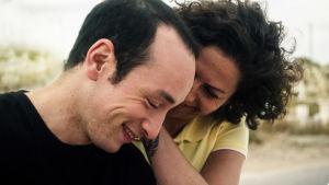 Nainen ja mies hymyilevät, katsovat alaspäin lähikuvassa.