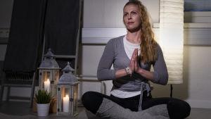 Nainen istuu jooga-asennossa.