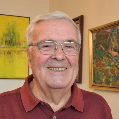 En man står i ett rum med olika tavlor på väggarna.