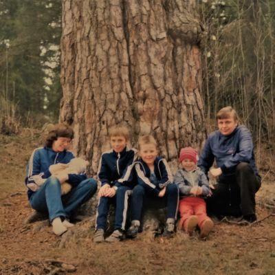 Perhe istuu ja poseeraa kameralle suuren männyn juurella: vasemmalla äiti sylissään vauva, keskellä kaksi kouluikäistä poikaa ja heitä nuorempi tyttö, oikealla isä.