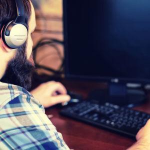 En person med hörlurar på jobbar framför en dator.