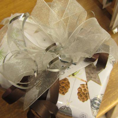 Joulupaketti jossa hopeanauhasta tehty rusetti.