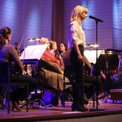 Nainen laulaa konserttilavalla.
