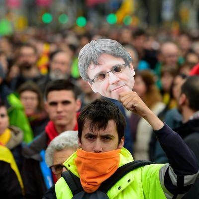 En demonstrant håller upp en pappersmask av Carles Puidgemont i Barcelona den 25 mars 2018.