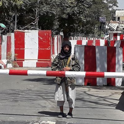 En talibankrigare står bakom en bom i staden Ghazni