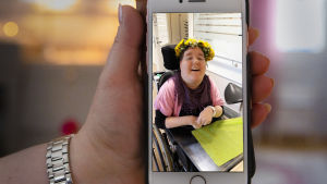 Maarit Pitkäsen kädessä olevassa puhelimessa on kuva hänen tyttärestään Veerasta, joka istuu pyörätuolissa päässään voikukkaseppele ja kasvoillaan iloinen hymy.