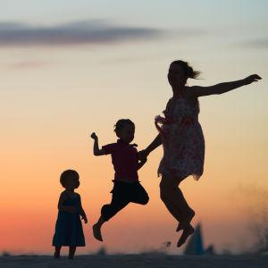 Tre personer i silhuett som hoppar med en solnedgång i bakgrunden.
