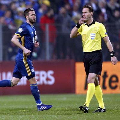 Miralem Pjanic löper bredvid matchens domare under Bosnien-Hercegovinas landskamp.