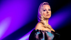 UMK-finalisti Sansa seisoo sinisen taustan edessä ja katsoo suoraan kameraan. Yllään vaaleahiuksisella Sansalla on petrolinvärisenä välkkyvä mekko.