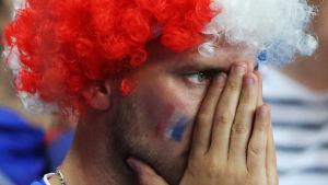 En fransk supporter efter EM-finalförlusten. Håller händerna framför näsan.