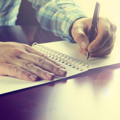 Person skriver i ett häfte