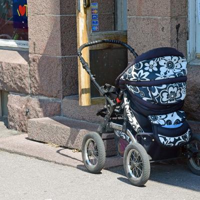 Barnvagn på gatan utanför affär.