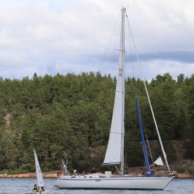 Små segelbåtar girar ute till havs samtidigt som stor segelbåt passerar dem.