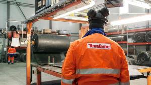 En Terrafame-medarbetare i orange rock övervakar en maskin.