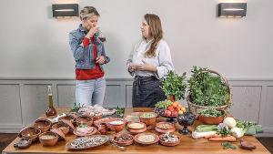 Ella Kanninen kokin kanssa ison pöydän ääressä, jossa on paljon ruokaa saviastioissa. Ella haistaa lasikannussa olevaa nestettä.