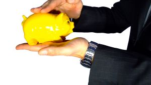 En hand håller i en gul spargris