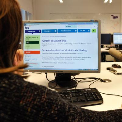 Person fotograferade bakifrån. På datorskärmen finns FPA:s hemsida med information om det allmänna bostadsbidraget.