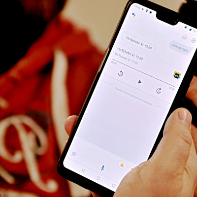 En hand håller i en telefon med Googles röststyrda assistent.